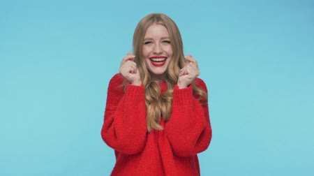 embarrassed : Cheerful pretty woman in sweater becoming touched and looking at the camera over turquoise background
