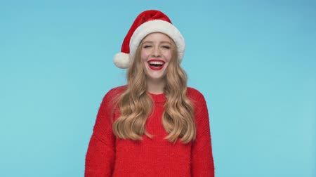 смущенный : Cheerful pretty woman in christmas hat laughing and looking at the camera over turquoise background