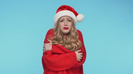 embarrassed : Unhappy pretty woman in christmas hat having cold and hugging herself over turquoise background