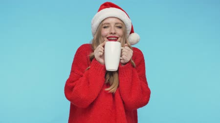 embarrassed : Happy pretty woman in christmas hat sniffing tea while holding cup and enjoying the moment over turquoise background Stock Footage