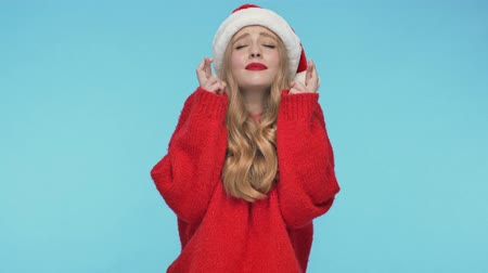embarrassed : Intrigued pretty woman in christmas hat praying with crossed fingers gestures over turquoise background