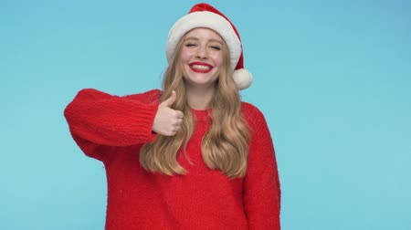 embarrassed : Cheerful pretty woman in christmas hat showing thumb up and looking at the camera over turquoise background