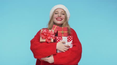 embarrassed : Pleased pretty woman in christmas hat holding gift boxes and enjoying this moment over turquoise background