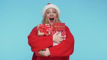 embarrassed : Surprised pretty woman in christmas hat holding gift boxes and becoming happy over turquoise background
