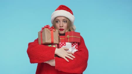 embarrassed : Displeased pretty woman in christmas hat standing with gift boxes over turquoise background