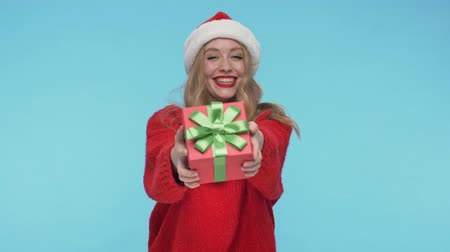 embarrassed : Cheerful pretty woman in christmas hat picking up a gift and rejoicing over turquoise background