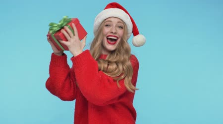 embarrassed : Cheerful intrigued pretty woman in christmas hat shaking a gift box and looking at the camera over turquoise background