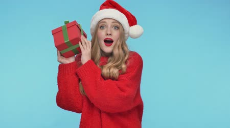 смущенный : Cheerful intrigued pretty woman in christmas hat guessing what is in the gift box while shaking it and becoming happy after that over turquoise background