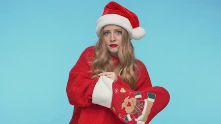 embarrassed : Intrigued pretty woman in christmas hat does not finding a gift and becoming sad after that over turquoise background Stock Footage