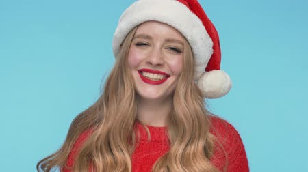 embarrassed : Close up view of Playful pretty woman in christmas hat playing with her hair and looking at the camera over turquoise background Stock Footage