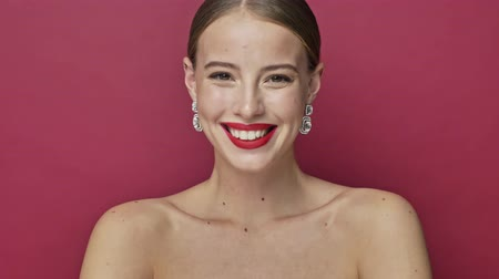 szminka : A lovely cheerful young woman with earrings and red lipstick laughing isolated over red background