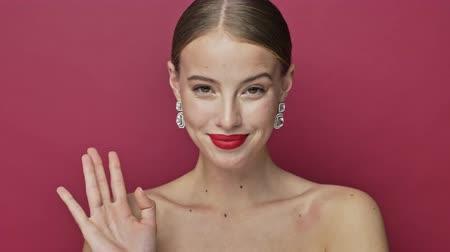 alluring : Flirty coquettish young woman with red lipstick and earrings is waving her hand isolated over red background