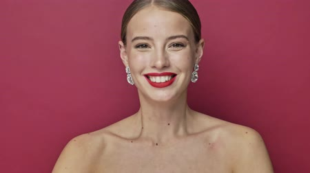 head over : Surprising cheerful young woman with red lipstick and earrings is pointing to the camera isolated over red background
