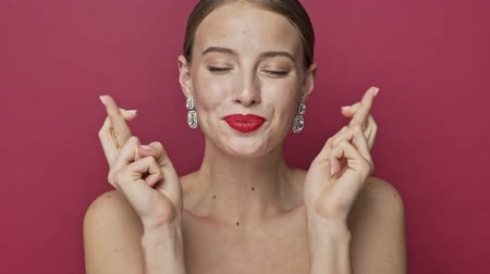 adorável : Smiling young woman with red lipstick and earrings is crossing her fingers like in praying gesture isolated over red background