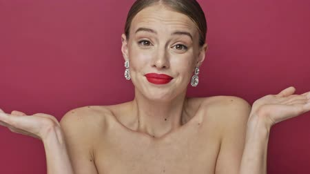 alluring : Pretty puzzled young woman with red lipstick and earrings is shrugging her shoulders over red background Stock Footage