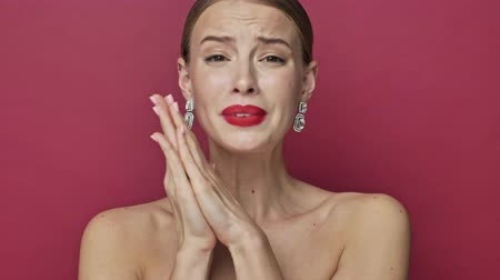söylemek : A nice young woman with red lipstick and earrings is doing a pray gesture and say please isolated over red background