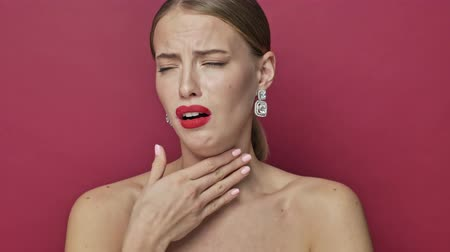fájó : A sick young woman with red lipstick and earrings is coughing while having a sore throat isolated over red background