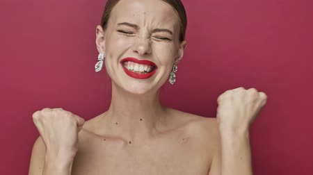 húszas évek : Happy surprised young woman with red lipstick and earrings is doing a winner gesture isolated over red background