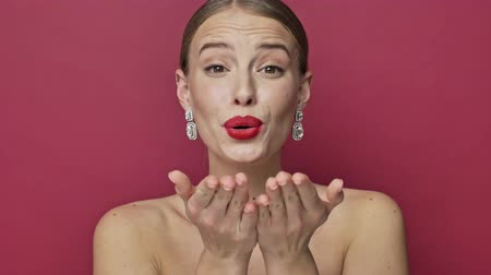 joyas : Lovely beautiful young woman with red lipstick and earrings is sending an air kiss to the camera isolated over red background