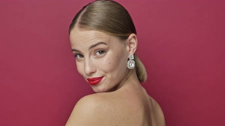 adorável : A joyful young woman with red lipstick and earrings is turning to the camera isolated over red background