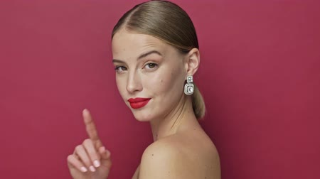 szminka : A flirty coquettish young woman with red lipstick and earrings is turning to the camera and doing a silence gesture isolated over red background