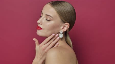 pat : Side view of young nice woman with red lipstick and earrings is stroking her shoulder isolated over red background