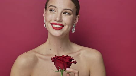 arete : Beautiful young woman with red lipstick and earrings is poising with a red rose flower isolated over red background Archivo de Video