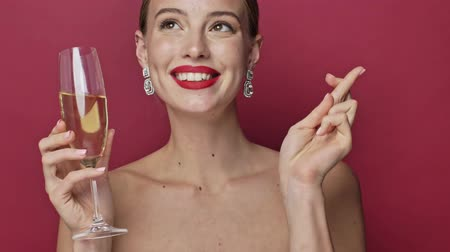 arete : Pretty young woman with red lipstick and earrings is making a wish while holding a glass of champagne isolated over red background Archivo de Video