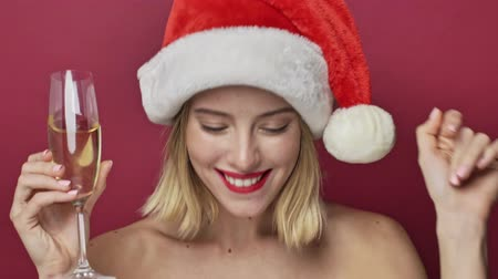 klauzule : Nice young woman with red lipstick wearing santa clause hat is dancing while holding a glass of champagne isolated over red background