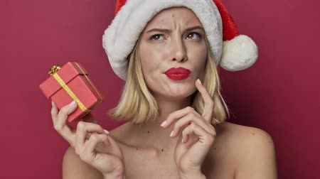szminka : Beautiful young woman with red lipstick wearing santa clause hat is guessing what is in the small present isolated over red background