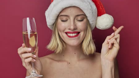 záradék : Pretty young woman with red lipstick wearing santa clause hat is making a wish while holding a glass of champagne isolated over red background