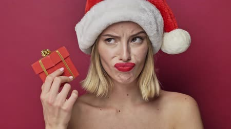 szminka : Displeased young woman with red lipstick wearing santa clause hat is guessing what is in the small present then throws it away isolated over red background