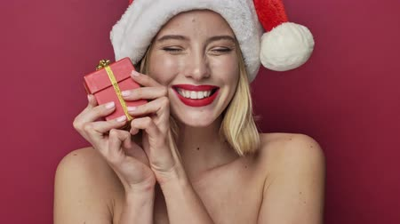 klauzule : Cheerful happy young woman with red lipstick wearing santa clause hat is holding a small present isolated over red background Dostupné videozáznamy