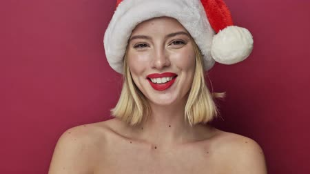 záradék : Joyful attractive young woman with red lipstick wearing santa clause hat is winking isolated over red background