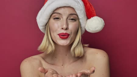 adorável : Nice attractive young woman with red lipstick wearing santa clause hat is sending an air kiss isolated over red background Stock Footage