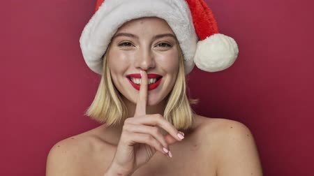 adorável : Positive young woman with red lipstick wearing santa clause hat is doing a silence gesture isolated over red background Stock Footage