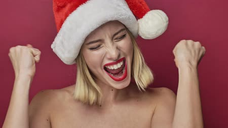 серьги : Attractive cheerful young woman with red lipstick wearing santa clause hat is doing a winner gesture isolated over red background