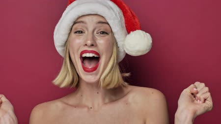 klauzule : Happy cheerful smiling young woman with red lipstick wearing santa clause hat is appearing isolated over red background Dostupné videozáznamy