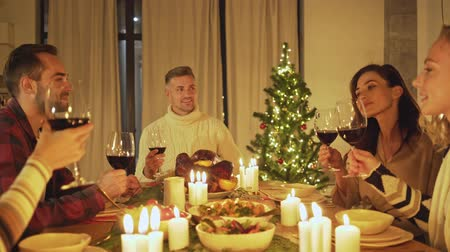 kırmızı şarap : Happy attractive friends raising glasses of red wine while celebrating christmas eve at home with traditional food and decoration