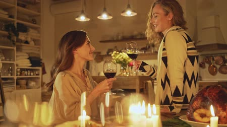 kırmızı şarap : Two attractive smiling girls talking to each other about something with glasses of red wine while celebrating christmas