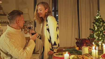 свечи : Attractive happy man and woman talking to each other then raising glasses and drinking wine at christmas time at home