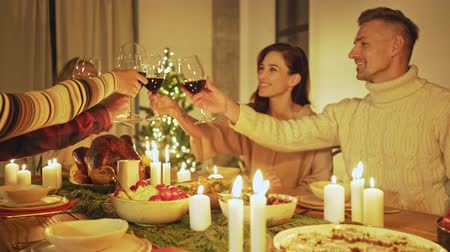 kırmızı şarap : Group of happy smiling friends raising glasses of red wine while celebrating christmas eve with traditional food and decoration