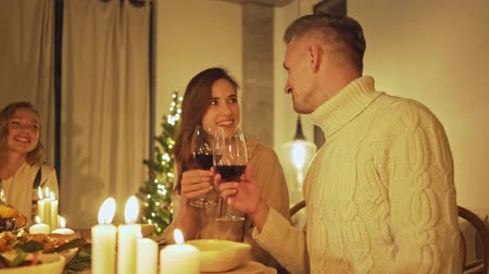 kırmızı şarap : Couple man and woman holding glasses of red wine while sitting at the festive table and celebrating christmas eve