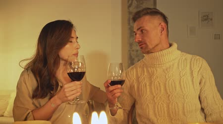 kırmızı şarap : Happy man and woman holding glasses of red wine and talking while sitting at the festive table and celebrating christmas eve
