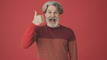 polegar : Happy elderly gray-haired bearded man in red sweater showing a thumb up gesture isolated over red wall