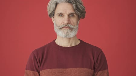 knitted : Happy elderly gray-haired bearded man in red sweater opening his eyes isolated over red wall Stock Footage