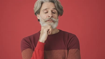 cavalheiro : Handsome gray-haired bearded man in red sweater thinking about something while looking around isolated over red wall