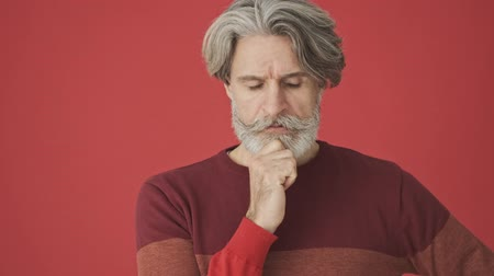 серый фон : Thinking gray-haired bearded man in red sweater pointing his finger up while finding a solution isolated over red wall