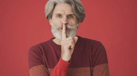 cavalheiro : Serious displeased gray-haired bearded man in red sweater doing a silence gesture isolated over red wall