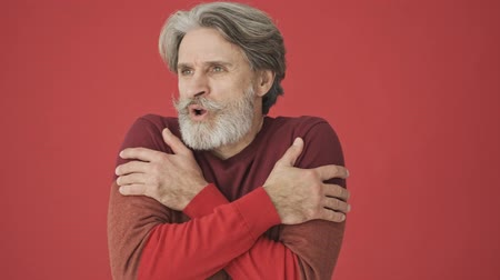 sofá : Frozen gray-haired bearded man in red sweater hugs himself while showing that he is cold isolated over red wall